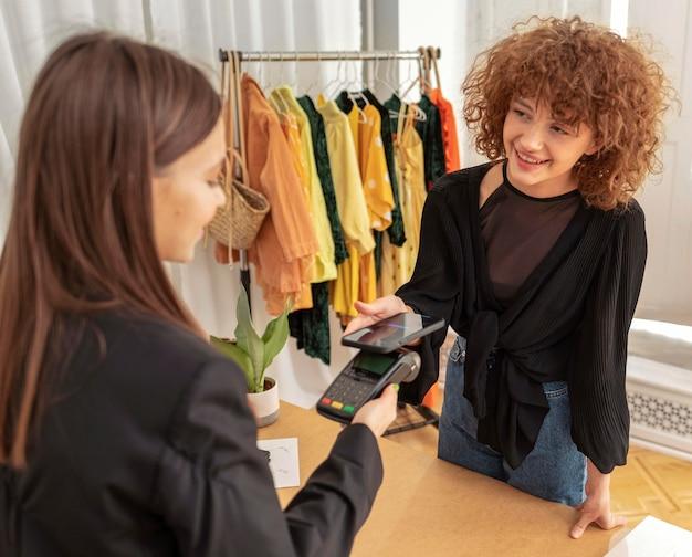 Vrouw die voor kleren betaalt