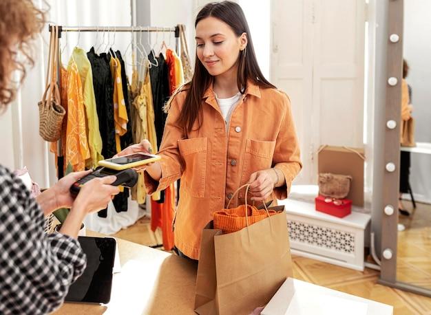 Vrouw die voor kleren bij opslag betaalt