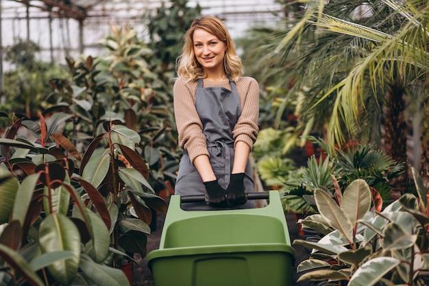 Vrouw die voor planten in een serre zorgen