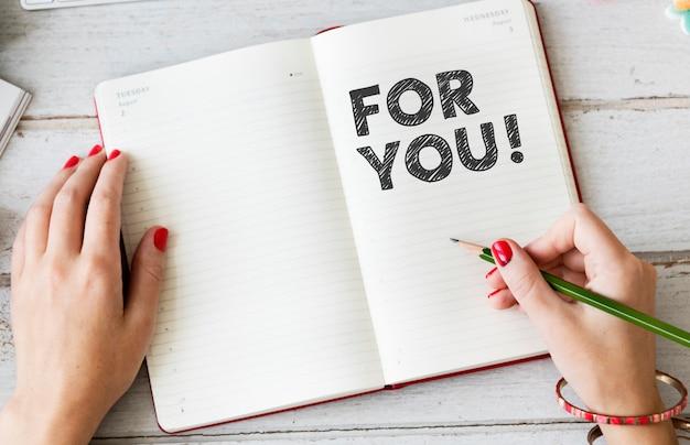 Vrouw die voor u op een notitieboekje schrijft