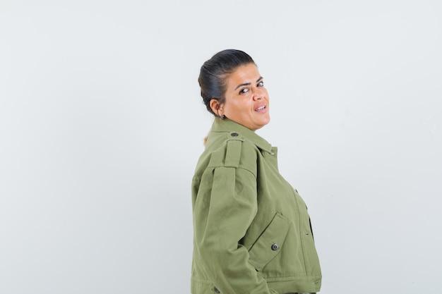 Vrouw die voorzijde in jasje, t-shirt bekijkt en elegant kijkt