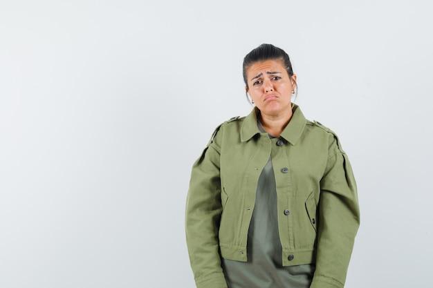 Vrouw die voorzijde in jasje, t-shirt bekijkt en nederig kijkt.