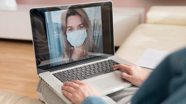 Vrouw die vriend videocalling draagt die masker draagt