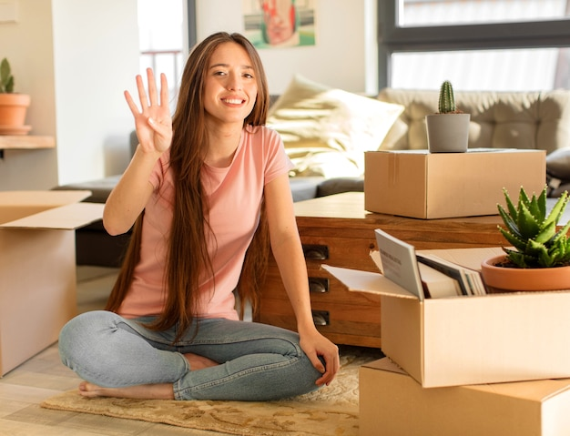 Vrouw die vriendelijk glimlacht en kijkt, nummer vier of vierde met vooruit hand toont, aftellend