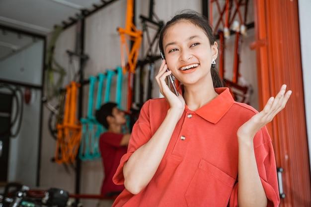 Vrouw die vrolijk lacht tijdens het chatten met een mobiele telefoon in een fietsenwinkel