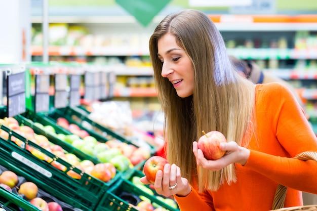Vrouw die vruchten in supemarket selecteren