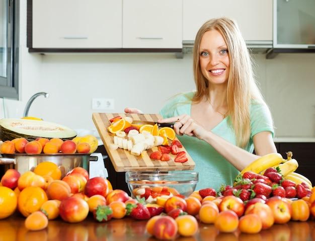 Vrouw die vruchten voor sala snijdt