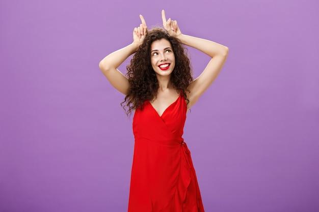 Vrouw die waaghals is op feest, sensueel en verleidelijk in rode elegante avondjurk met i...