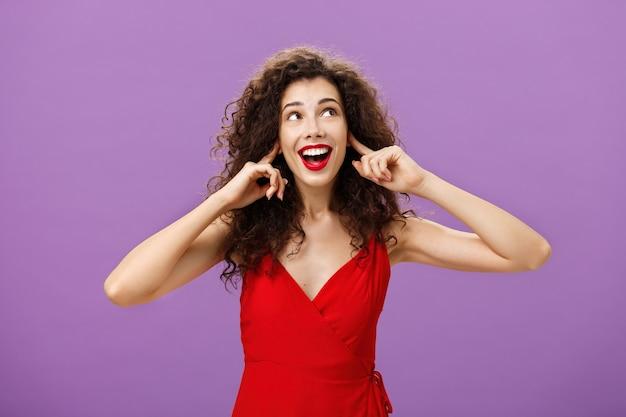 Vrouw die wachtte vermaakt op luide knal en vuurwerk glimlachend breed starend naar de rechterbovenhoek die oren bedekt met wijsvingers, gecharmeerd in luxe rode jurk en avondmake-up.
