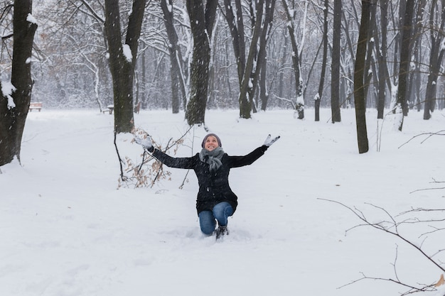 Vrouw die warme kleren draagt die van in bos genieten