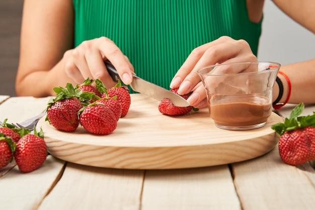 Vrouw die wat aardbeien snijdt om ze in chocolade te nemen.