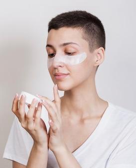 Vrouw die wat gezichtscrème gebruikt om te hydrateren