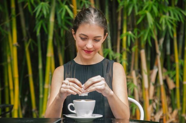 Vrouw die wat koffie drinkt bij een terras in frankrijk