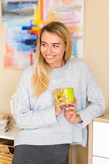 Vrouw die weg en een kop van koffie houdt kijkt