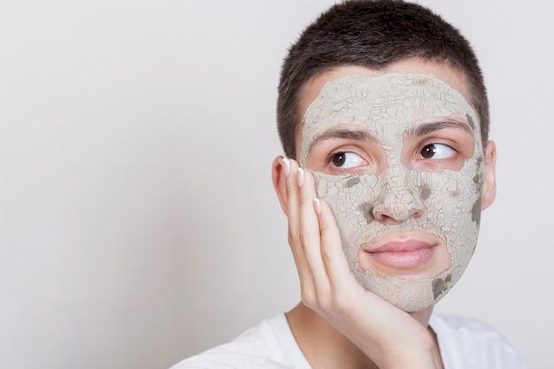 Vrouw die weg met gezichtsmodderbehandeling kijkt