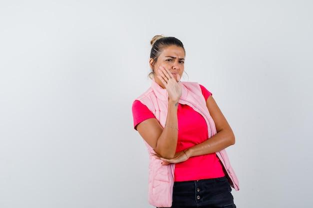Vrouw die weigeringsgebaar in t-shirt, vest toont en er serieus uitziet?