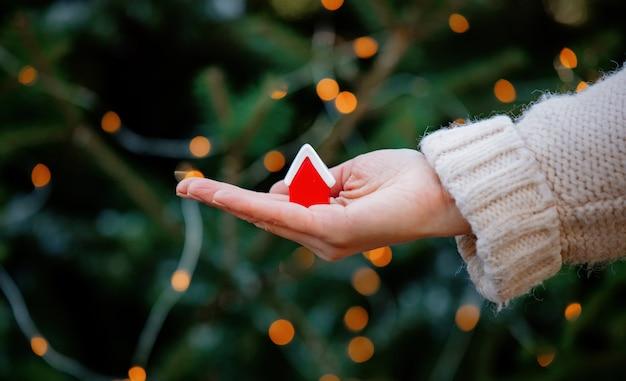Vrouw die weinig rood huis in hand op kerstmislichten en spar houden