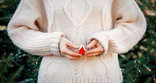 Vrouw die weinig rood huis in handen op kerstmislichten en spar houden