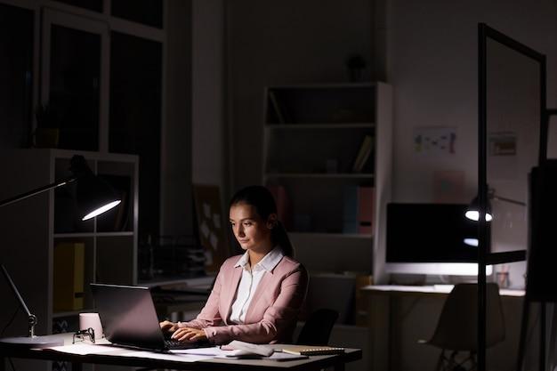 Vrouw die werkt in een donkere kantoor
