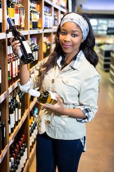Vrouw die wijnfles bekijken in kruidenierswinkelsectie bij supermarkt