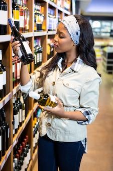 Vrouw die wijnfles bekijkt in kruidenierswinkelsectie
