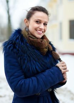Vrouw die winterjas draagt bij winterse straat