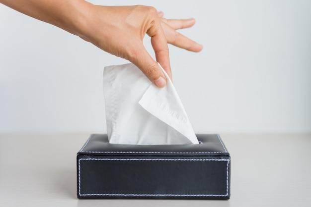 Vrouw die wit papieren zakdoekje van weefseldoos met de hand plukt.