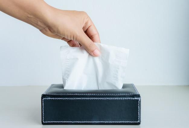Vrouw die wit papieren zakdoekje van weefseldoos met de hand plukt