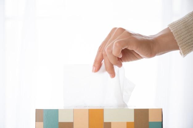 Vrouw die wit papieren zakdoekje van weefselvakje met de hand plukken. gezondheidszorg concept.
