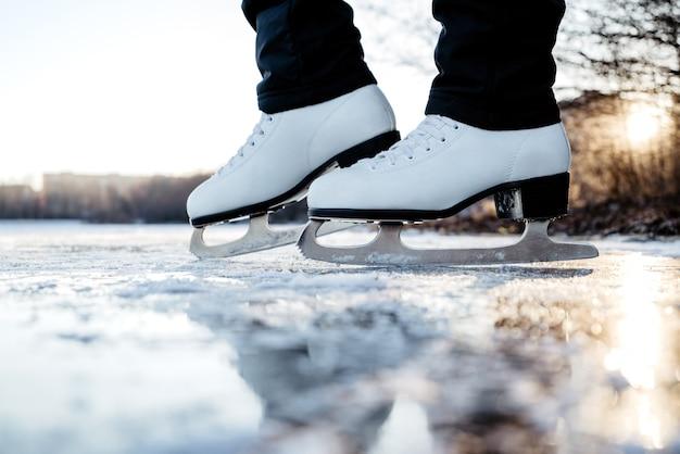 Vrouw die witte fugure schaatsen draagt ?? staat op ijs. winter buitensportactiviteiten