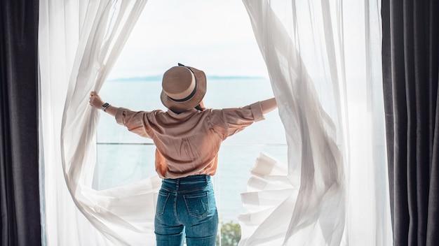 Vrouw die witte gordijnen opent, geniet van uitzicht op zee.