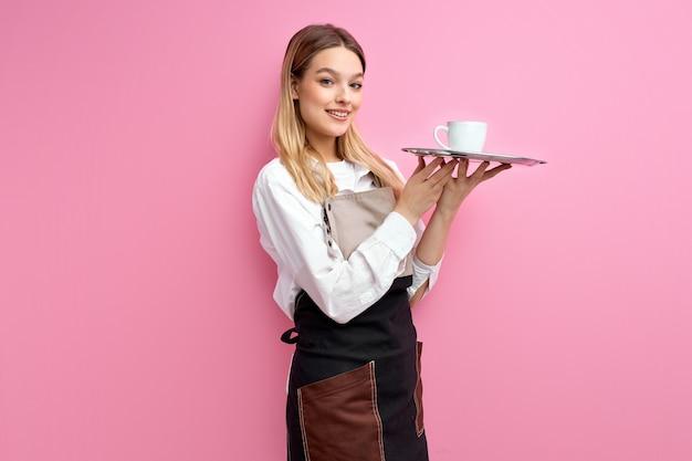 Vrouw die witte klassieke kop voor koffie of thee op dienblad houdt dat over roze studioachtergrond wordt geïsoleerd.