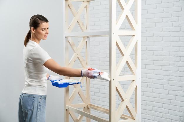 Vrouw die witte kleur met borstel op houten plank toepast