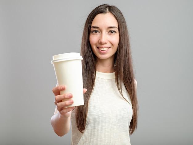 Vrouw die witte kop van koffie aanbiedt