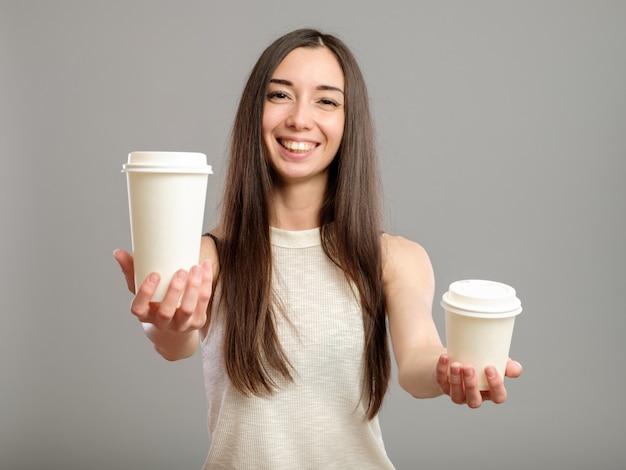 Vrouw die witte koppen van koffie aanbiedt