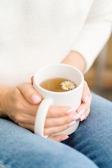 Vrouw die witte mok met thee en bloem houdt