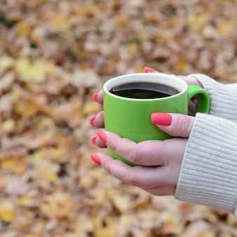 Vrouw die witte sweater draagt die een groene koffiekop houdt