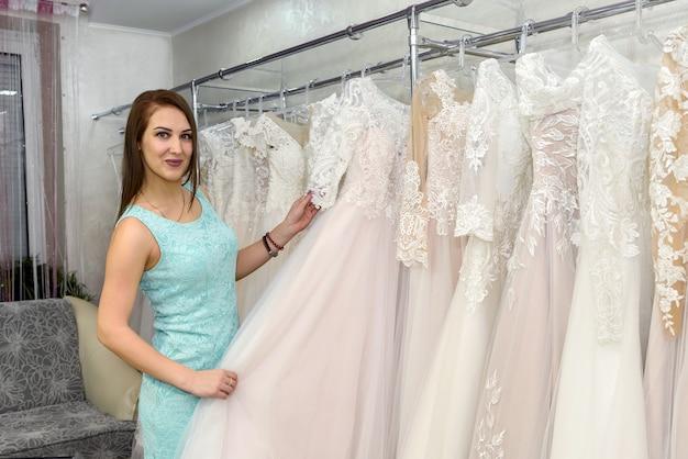 Vrouw die witte trouwjurk kiest in de bruidwinkel