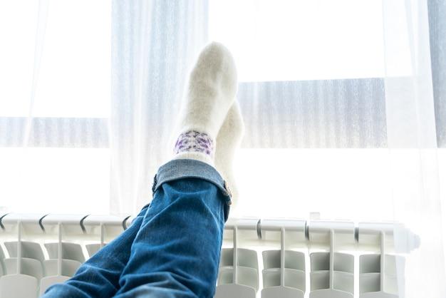 Vrouw die wollen sokken met voeten op verwarmer draagt