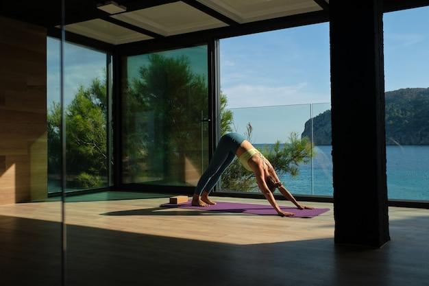 Vrouw die yoga beoefent in een naar beneden gerichte hondhouding