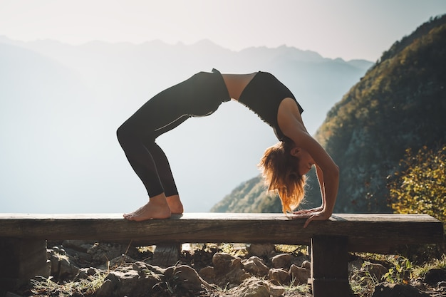 Vrouw die yoga beoefent op de natuur jonge vrouw mediteert op de achtergrond van bergen