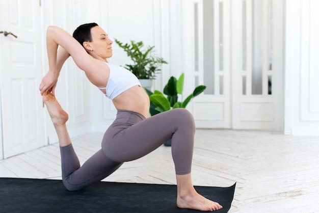 Vrouw die yoga beoefent op haar minimale witte huisachtergrond