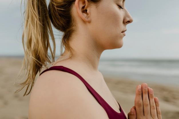 Vrouw die yoga beoefent op het strand