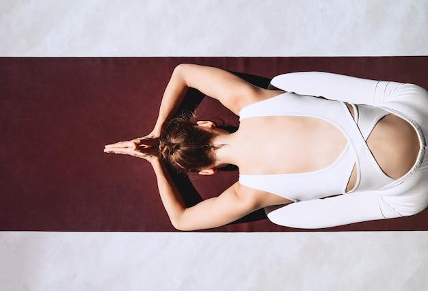 Vrouw die yoga beoefent op yogamat binnenshuis meisje mediteert en doet ontspannende yogahoudingen thuis