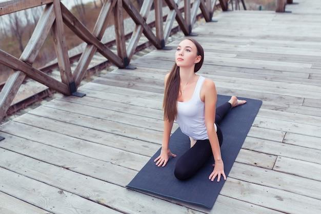 Vrouw die yoga beoefent, stelt buiten over hemel en houten brugachtergrond, kopieer ruimteconcept.