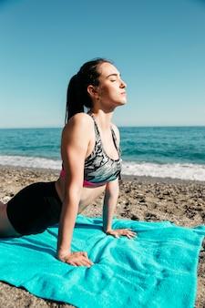 Vrouw die yoga doet bij het strand