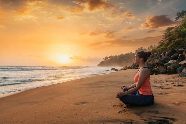 Vrouw die yoga doet bij strand - de padmasana-lotusbloem stelt