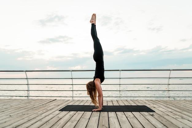 Vrouw die yoga doet en zich op haar handen dichtbij het overzees in de ochtend bevindt