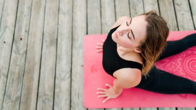 Vrouw die yoga in de ochtend doet en op een mat buigt