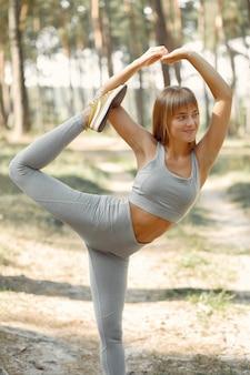 Vrouw die yoga in een de zomerbos doet